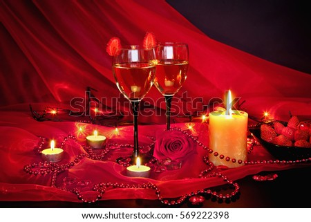 A romantic evening by candlelight. Glasses of champagne with strawberries, red roses and jewelry on a black background. Red black still life. Valentine's Day.