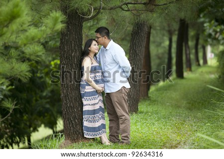 A romantic husband kissing his pregnant wife under pine tree