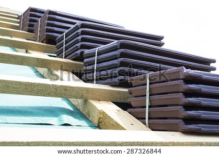 A roof under construction. Stacks of tiles ready to be fasten on the wooden construction. Waterproof and solid rooftop. - stock photo