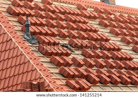 A roof under construction with stacks of roof tiles ready to fasten - stock photo