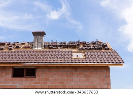 A roof with chimney under construction with stacks of roof tiles ready to fasten - stock photo