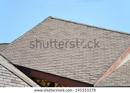 A rooftop of brown slate shingles in the sun - stock photo