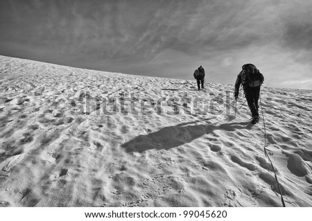 A Rope Team of Mountaineers Climbs Towards the Summit - stock photo