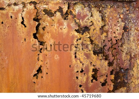 A rotted metal panel covered in rust. - stock photo