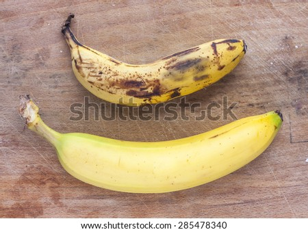 A rotten and a fresh ripe banana side by side on a mottled wooden surface - stock photo