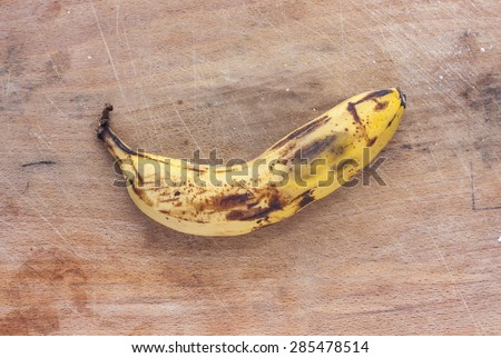 A rotten banana on a dirty mottled wooden surface - stock photo