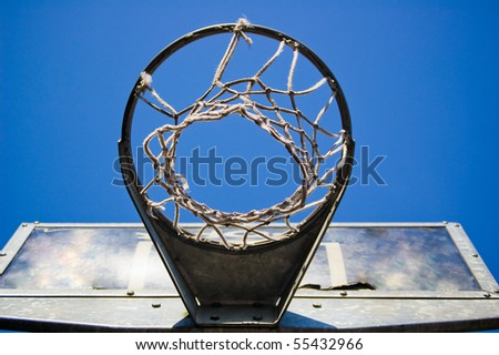 A rough basketball hoop from underneath, with clear blue sky. - stock photo