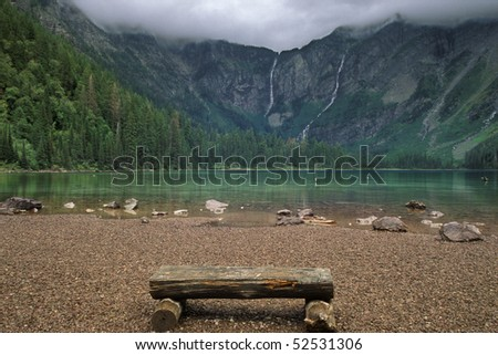 A rough hewn wood bench made of logs  sits on the rocky shore of Avalanche Lake in the mountains of Glacier National Park, Montana. Low clouds can be seen at the top of the frame. Horizontal shot. - stock photo