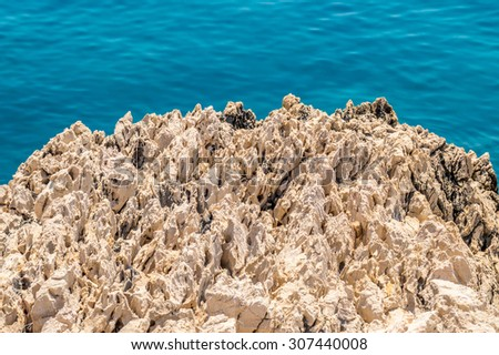 A rough textured spiky rock by the crystal clear blue Adriatic sea - stock photo