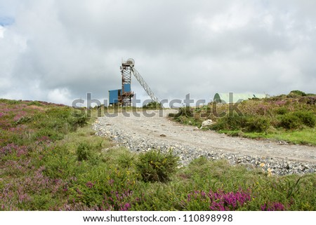A rough track cuts through scrubland towards a blue covered minehead winding gear structure.