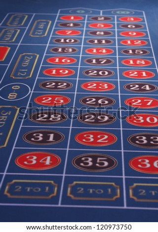 A roulette table in a casino with blue felt - stock photo