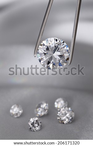 A round brilliant cut diamond held in tweezers - stock photo