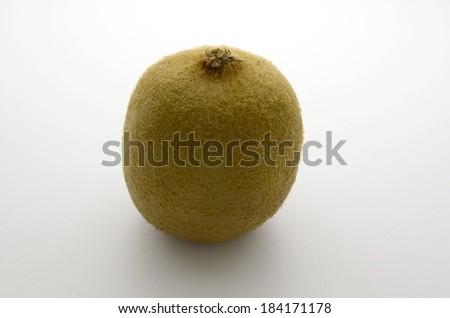 A round, fuzzy kiwi fruit sits by itself. - stock photo