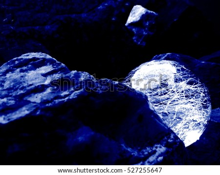 A Round Glass Glowing Ball between the Rocks