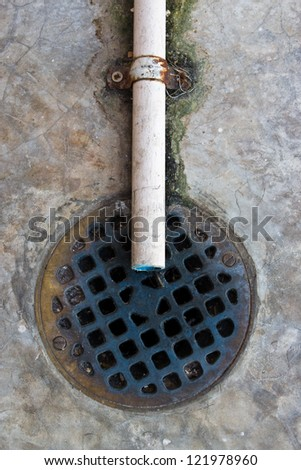 A round grille sewage and plastic water pipe. - stock photo