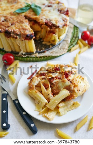 a round macaroni casserole with cheese on the piece of parchment - stock photo