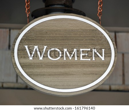 A round wooden sign that reads Women - stock photo