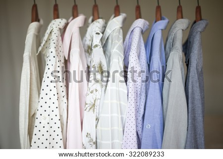 A row of assorted business shirts for women on hangers in a closet.
