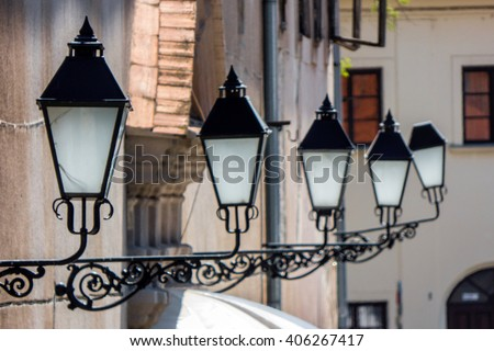 A row of baroque street lamps.  Odd one out.