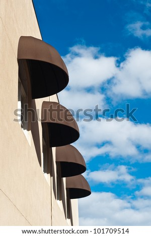 A row of brown awnings against a cloudy blue sky
