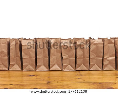 A row of brown paper bags against a white wall and a hard wood floor. - stock photo