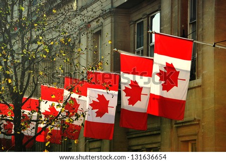 a row of Canadian flags outside Canada House in Trafalgar Square, London - stock photo