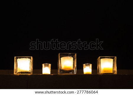 A row of candles in glass holders lined up along the top of a cement wall on a warm Arizona evening - stock photo