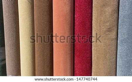 A row of carpets for sale at a flooring retail outlet. Possible background use. - stock photo