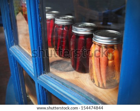 A row of carrots and parsnips pickled in mason jars is displayed in a glass window cabinet with blue frames. - stock photo