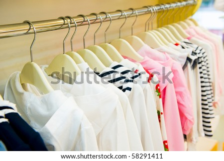 A row of children clothes hanging on hangers. - stock photo