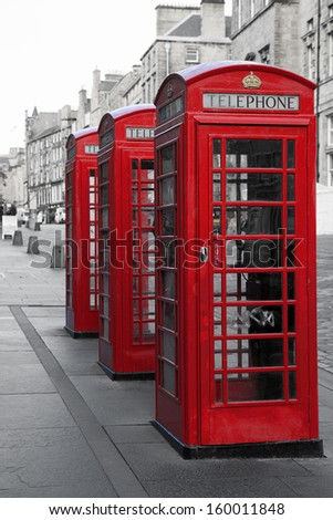 A row of classic British phone boxes on The Royal Mile, Edinburgh, Scotland. Retro effect in black and white with red - stock photo