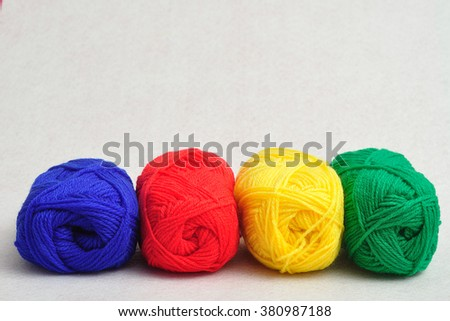 A row of colorful balls of wool isolated on a white background