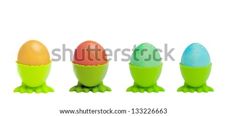 A row of colorful Easter eggs in green cups