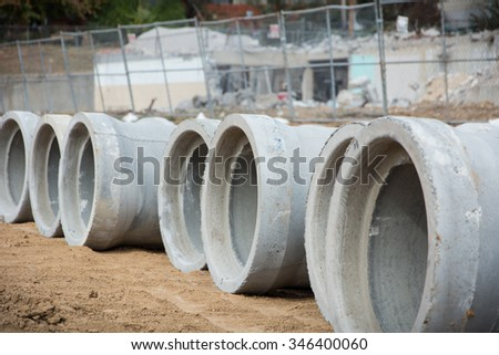 A row of concrete drain pipe sections stand ready to be installed. - stock photo