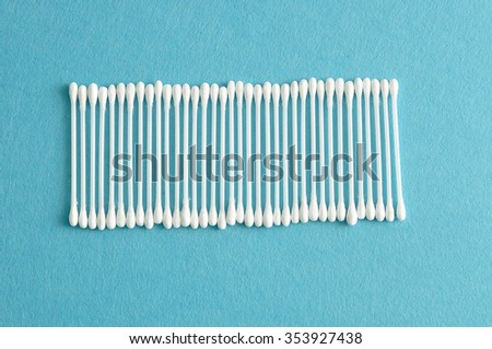 A row of cotton swabs isolated on a light blue background - stock photo