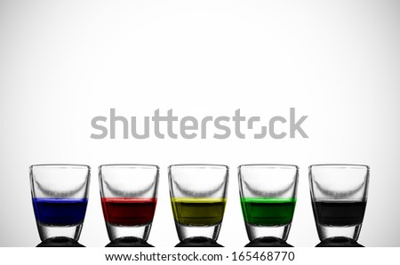A row of cups with colorful liquor.  - stock photo