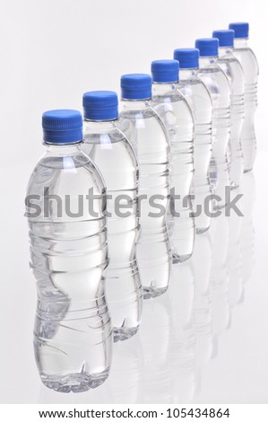a row of eight water bottles viewed from above - stock photo