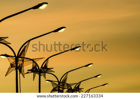 A row of electric posts with Christmas star decorations - stock photo