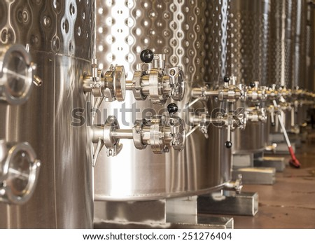 A row of fermentation tanks in a winery showing the valves and knobs used to control the flow of wine. - stock photo
