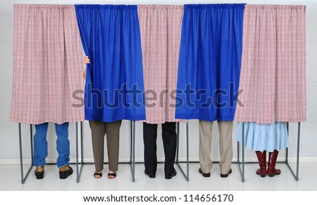 A row of five voting booths with men and women casting their ballots at a polling place. Horizontal format, only showing the legs of the voters, people are unrecognizable.. - stock photo