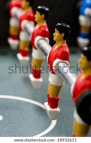 a row of Foosball or table soccer playing pieces - stock photo