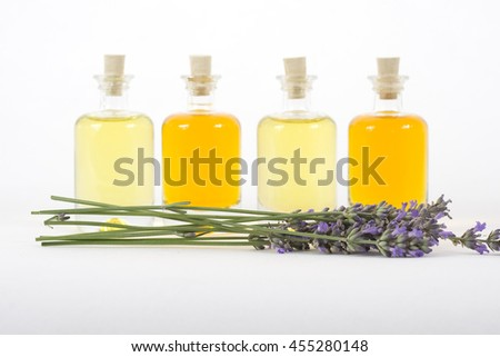 A row of four aromatherapy bottles with lavender on a white background - stock photo