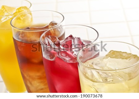 A row of four bright colored fruit drinks. - stock photo