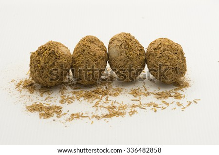 A row of four century eggs on white background. Chinese delicacy of preserved egg covered in a mixture of clay, ash, salt, quicklime, and rice hulls for several weeks to months. - stock photo