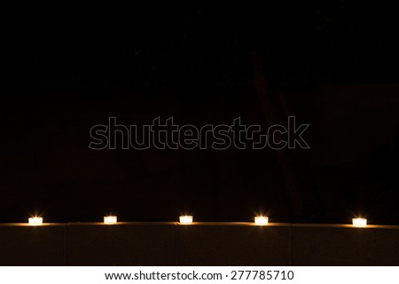 a row of glowing tealights lined up on top of a cement wall glow in high contrast to the blackness of the night - stock photo