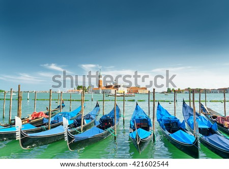 A row of gondolas parked beside the Riva degli Schiavoni in Venice, Italy. Beautiful view of the Venetian Lagoon. The Church of San Giorgio Maggiore on island of the same name is visible in background - stock photo