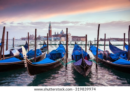 A row of gondolas parked beside the Riva degli Schiavoni in Venice, Italy. View of the Venetian Lagoon. The Church of San Giorgio Maggiore on island of the Venice, Italy, Europe - stock photo