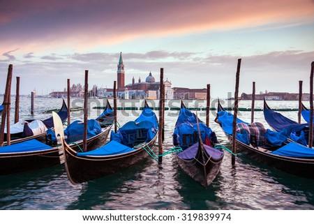 A row of gondolas parked beside the Riva degli Schiavoni in Venice, Italy. View of the Venetian Lagoon. The Church of San Giorgio Maggiore on island of the Venice, Italy, Europe - stock photo