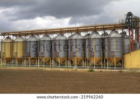 A row of grain silos surrounded by fields  - stock photo