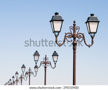 A row of lanterns runs along a beach-side promenade in southern France. - stock photo
